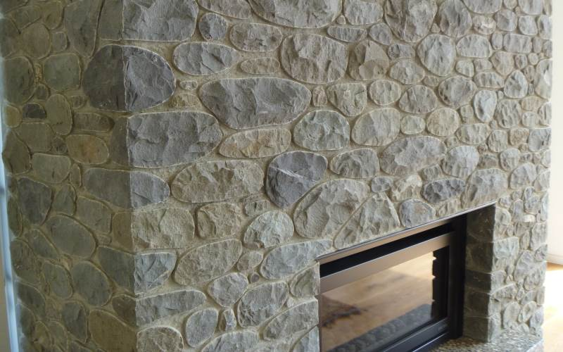 Split riverstone fireplace with recessed mortar joints