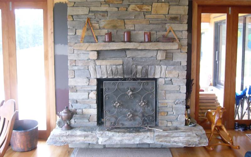 Tight stack schist with  counter levered hearth, sprung flat lintel, stone corbels supporting stone mantle.